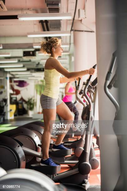 Young woman exercising on stair climbing machine in a gym.