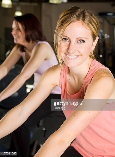 young woman exercising on stationary bike - rich_legg stock photos and pictures