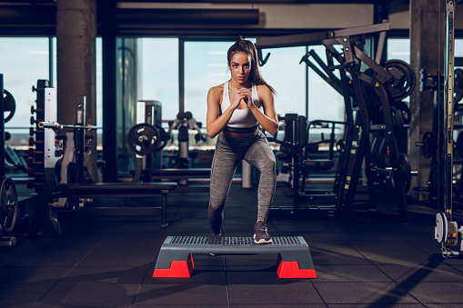 Young woman exercising on step aerobics equipment at gym 1064106354