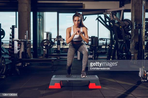 young woman exercising on step aerobics equipment at gym - palestra club ginnico foto e immagini stock
