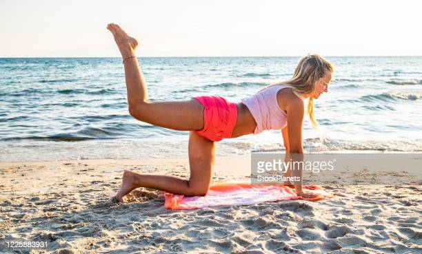 young woman exercising on the beach - human leg stock pictures, royalty-free photos & images