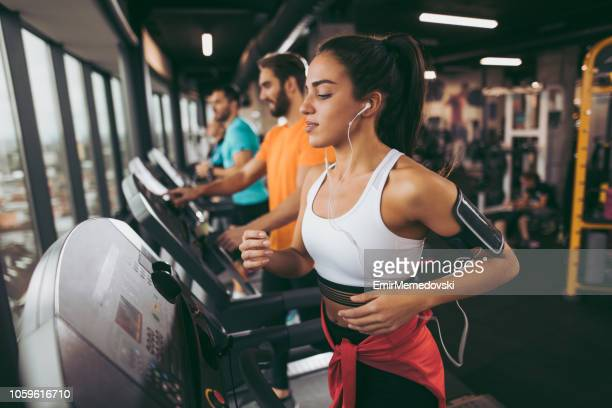 young woman exercising on treadmill - gym stock pictures, royalty-free photos & images