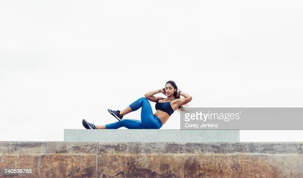 young woman exercising outdoors, doing sit-ups, south point park, miami beach, florida, usa - sit ups stock photos and pictures