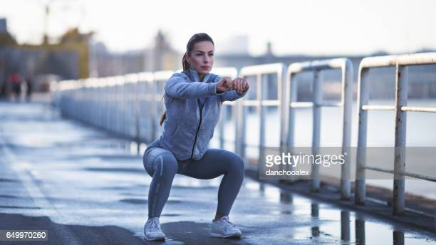 young woman exercising outdoors - warming up stock pictures, royalty-free photos & images