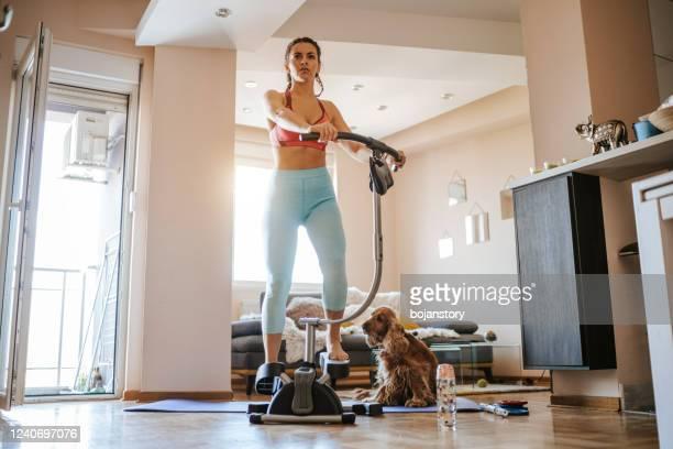 自宅でカーディオツイスターで運動する若い女性 - 有酸素運動 ストックフォトと画像
