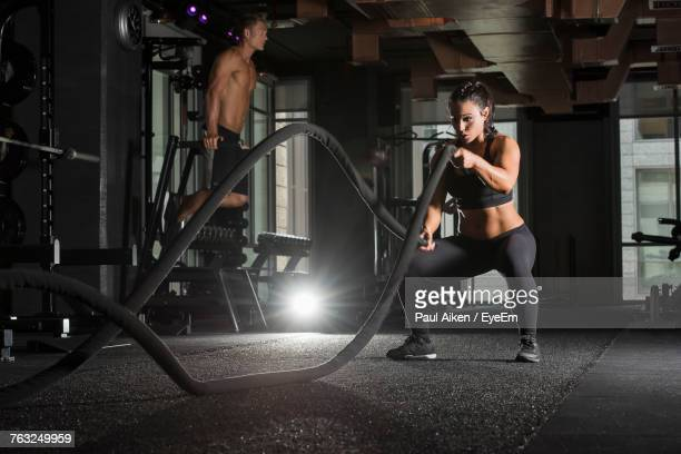 Young Woman Exercising With Battle Ropes While Man In Background At Gym