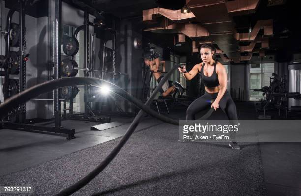 young woman exercising with battle ropes while man in background at gym - aikāne stock pictures, royalty-free photos & images