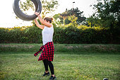 young woman exercising with car tire