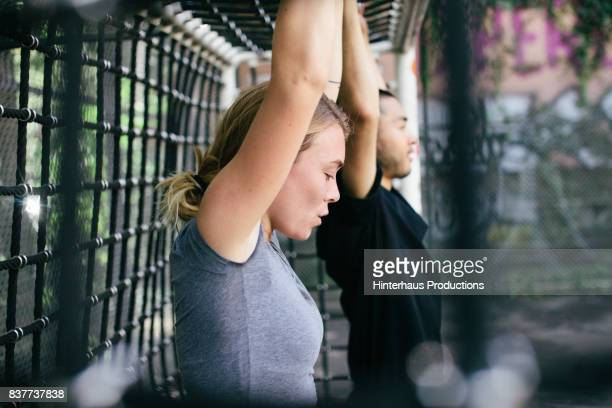 young woman exercising with colleague outdoors - ausdauer stock-fotos und bilder