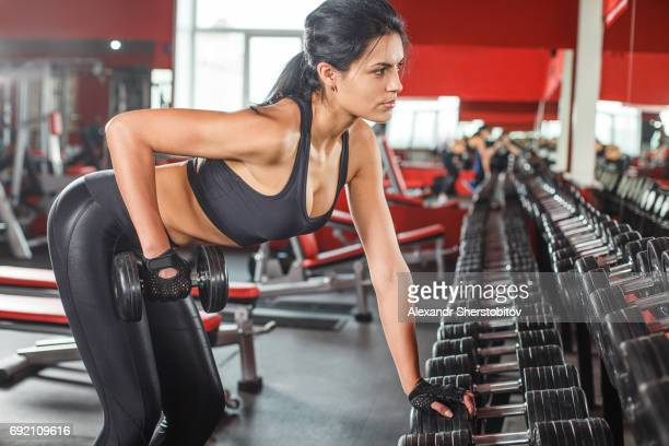 Young woman exercising with dumbbells at gym