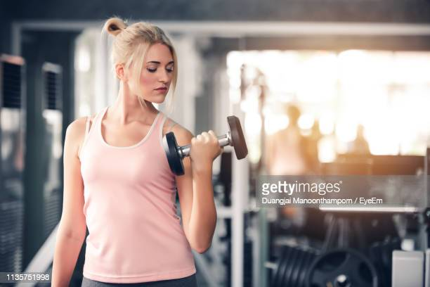 young woman exercising with dumbbells in gym - dumbbell stock pictures, royalty-free photos & images