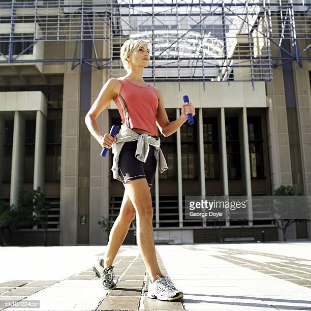 young woman exercising with dumbbells - ランニングショートパンツ ストックフォトと画像