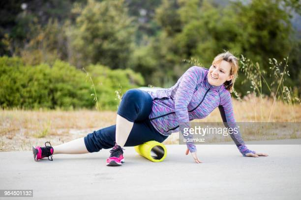 young woman exercising with foam roller - de rola imagens e fotografias de stock