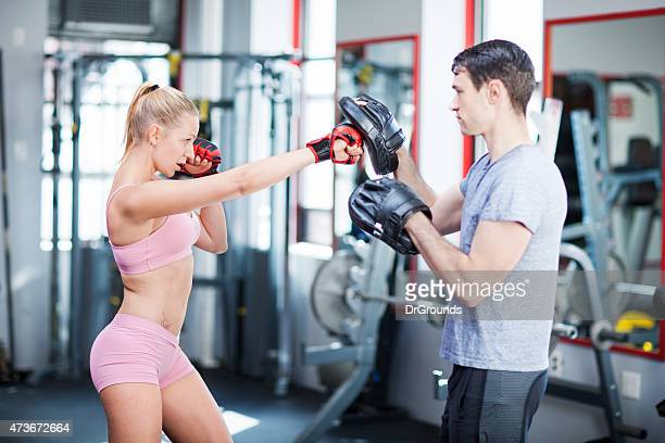 young woman exercising with instructor - padding stock photos and pictures