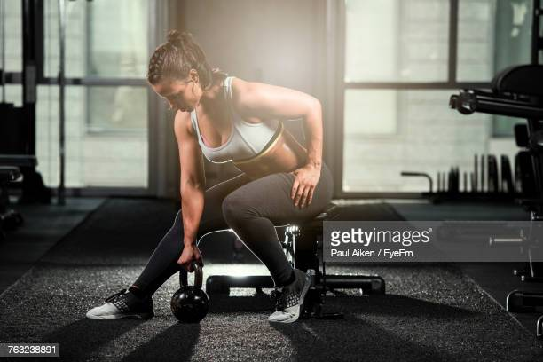 young woman exercising with kettlebell at gym - aikāne stock pictures, royalty-free photos & images