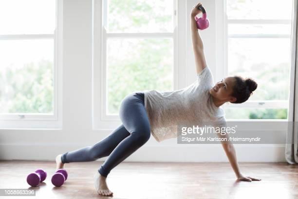 young woman exercising with kettlebell at home - interior de casa imagens e fotografias de stock