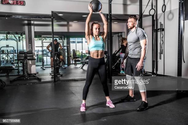 jonge vrouw uitoefenend met medicijnbal terwijl fitness instructeur haar helpt - gewichtheffen krachttraining stockfoto's en -beelden