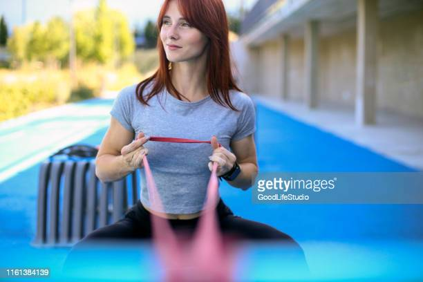 young woman exercising with resistance band - strap stock pictures, royalty-free photos & images