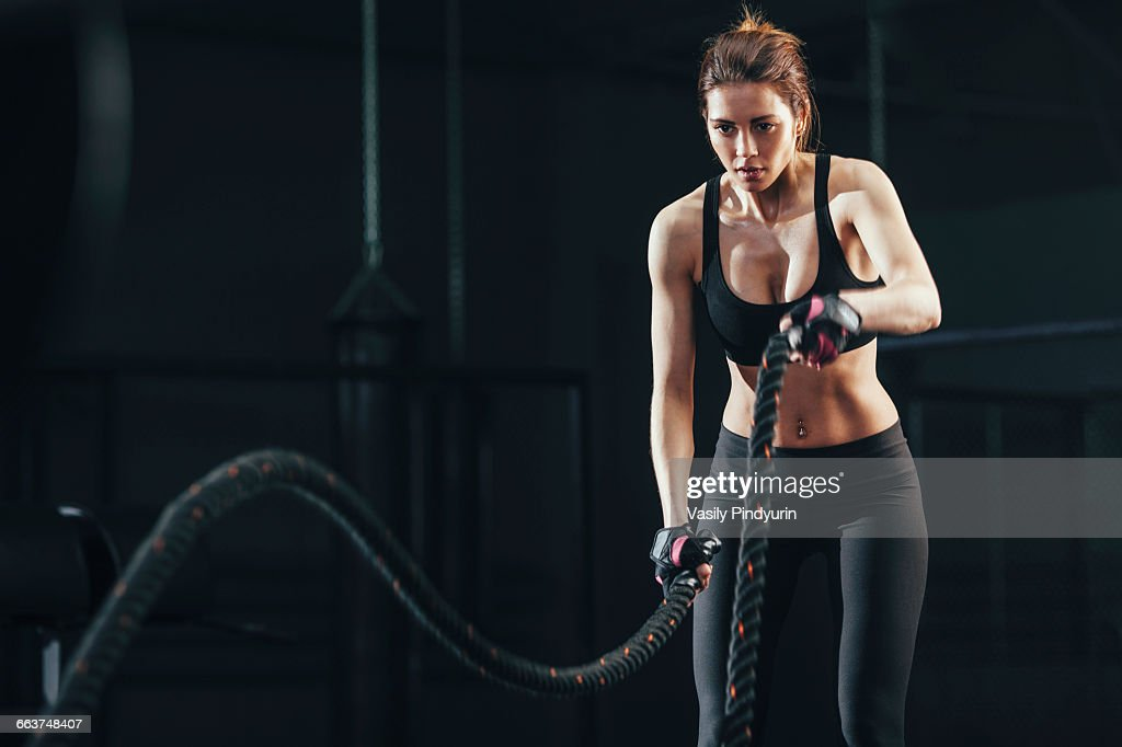 Young woman exercising with rope at gym : Stock Photo