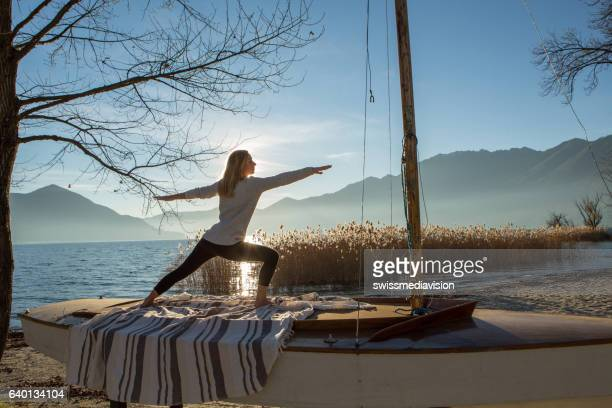 Young woman exercising yoga by the lake at sunset