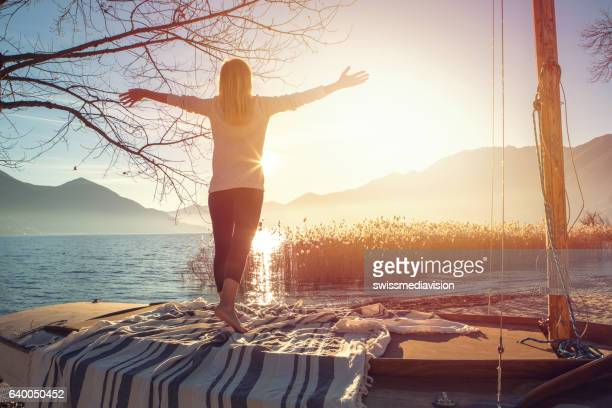young woman exercising yoga by the lake - ascona stock photos and pictures