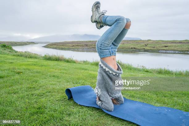 若い女性の自然で倒立ポーズを取るヨガを行使