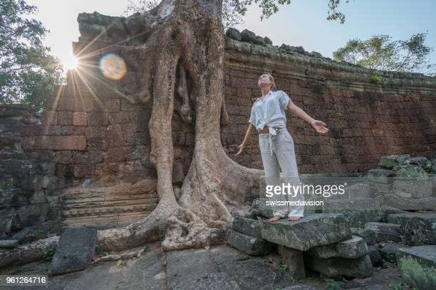 Young woman exercising yoga in ancient temple near majestic tree roots; sunlight passing through and relaxing with some meditation; concept of people with healthy lifestyles and wellbeing and travel