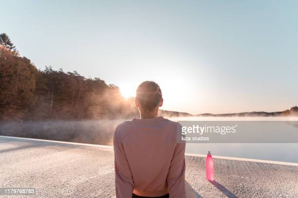 young woman exercising yoga in the early morning - al centro foto e immagini stock