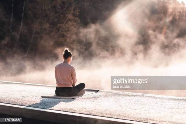 mujer joven haciendo ejercicio yoga en la madrugada - espiritualidad fotografías e imágenes de stock