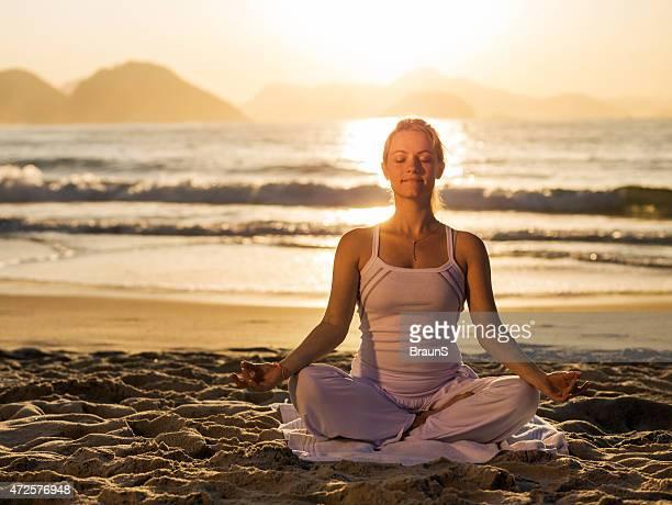 Junge Frau Ausübung Yoga am Strand bei Sonnenuntergang.