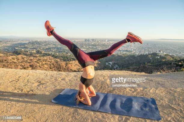 young woman exercising yoga upside down position holding headstand at sunset - hollywood california stock pictures, royalty-free photos & images