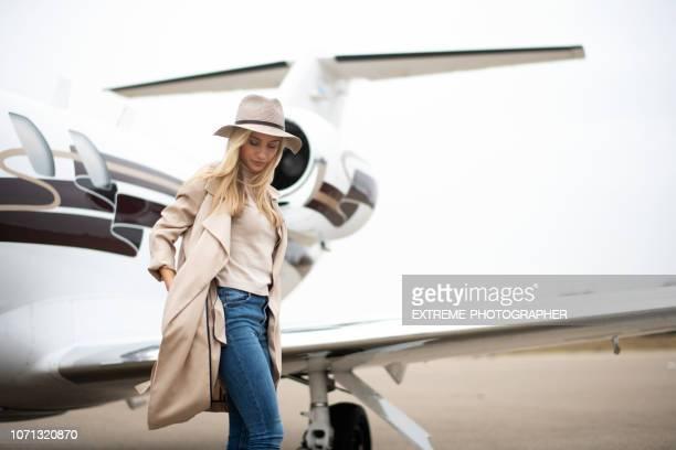 mujer joven salir de un avión privado - alta sociedad fotografías e imágenes de stock