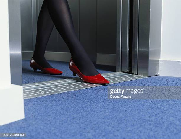 Young woman exiting lift, low section