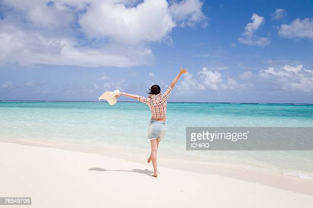 Young woman expanding hands on beach, rear view