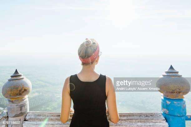 Young woman explores Buddhist temple, above plain