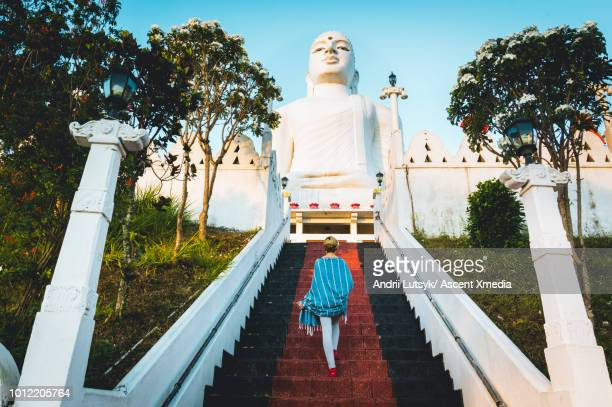 young woman explores buddhist temple grounds - eskapismus stock-fotos und bilder