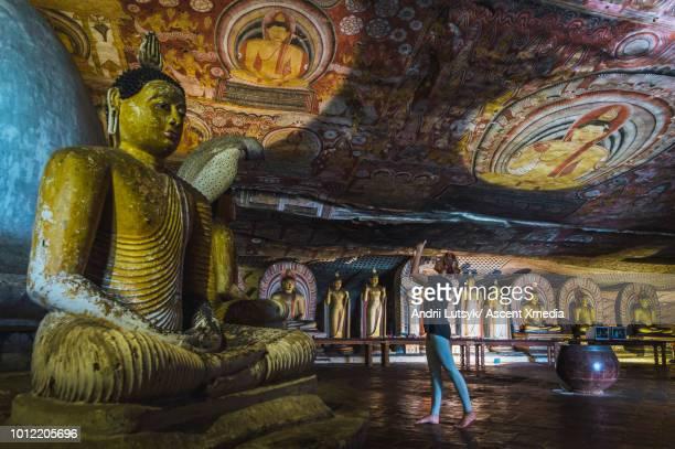 young woman explores buddhist temple, in cave - sri lanka fotografías e imágenes de stock