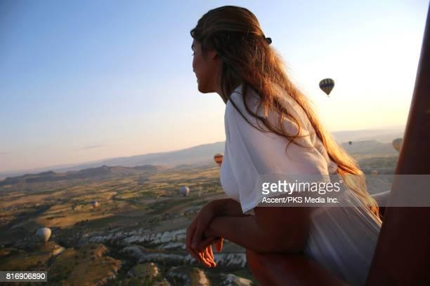 Young woman explores Cappadocia landscape from hot air balloon