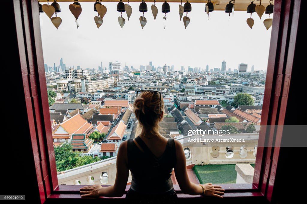 Young woman explores city, looks out from overview : Stock Photo