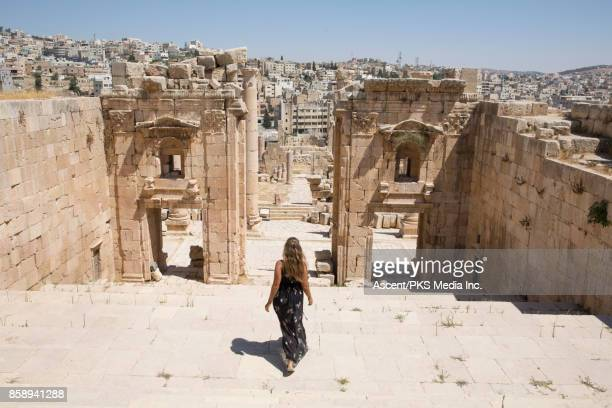 young woman explores desert ruins from natural corridor - long dress stock pictures, royalty-free photos & images