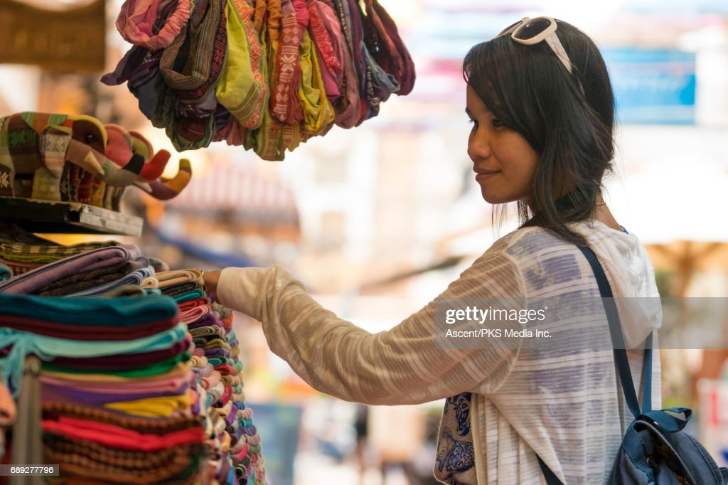 Young woman explores market, local colour : Stock Photo