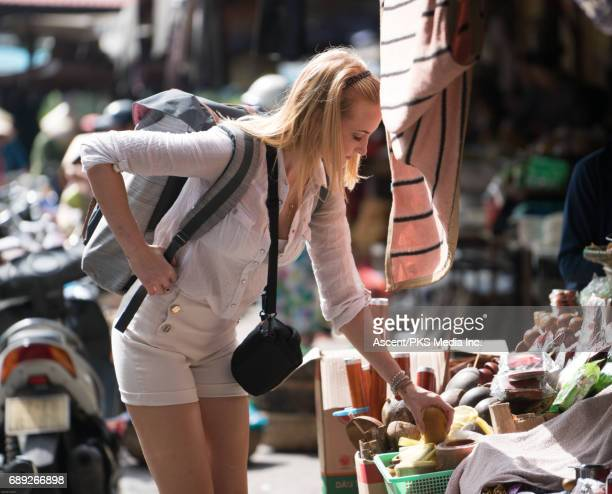 Young woman explores market, with locals