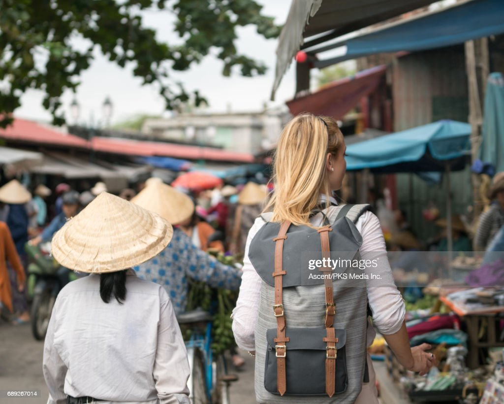 Young woman explores market, with locals : Stock Photo