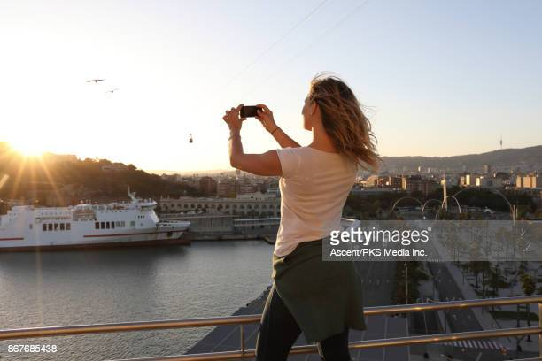Young woman explores seafront harbour area of city, Barcelona