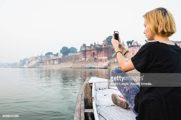 Young woman explores the Ganges by boat
