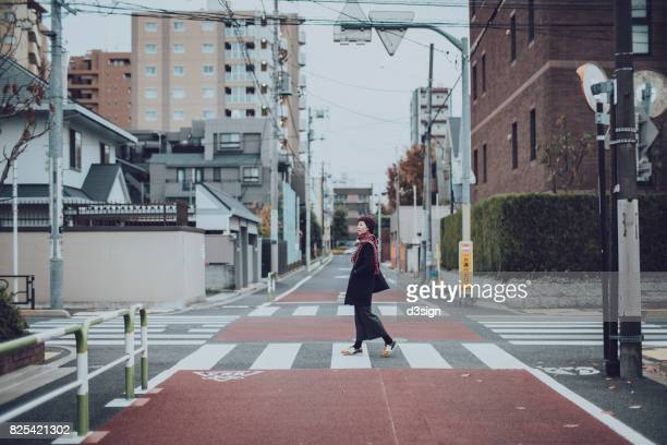 Young woman exploring and walking through local streets in Tokyo, Japan