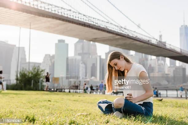 young woman exploring new york city, taking a break, reading book - brooklyn bridge park stock-fotos und bilder