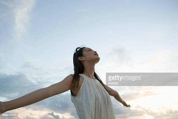 young woman extending her arm to sky, eyes closed - 息抜き ストックフォトと画像