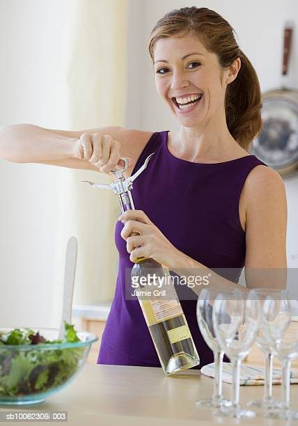 Young woman extracting cork from bottle of white wine, smiling, portrait