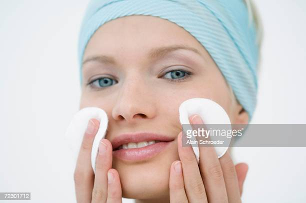 Young Woman face using a cleansing cotton on her cheeks, close-up (studio)